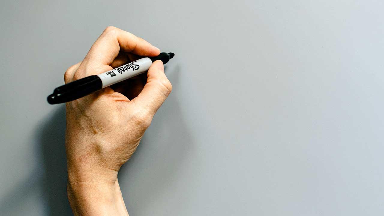 Linkshänder hält Stift auf leeres Blatt
