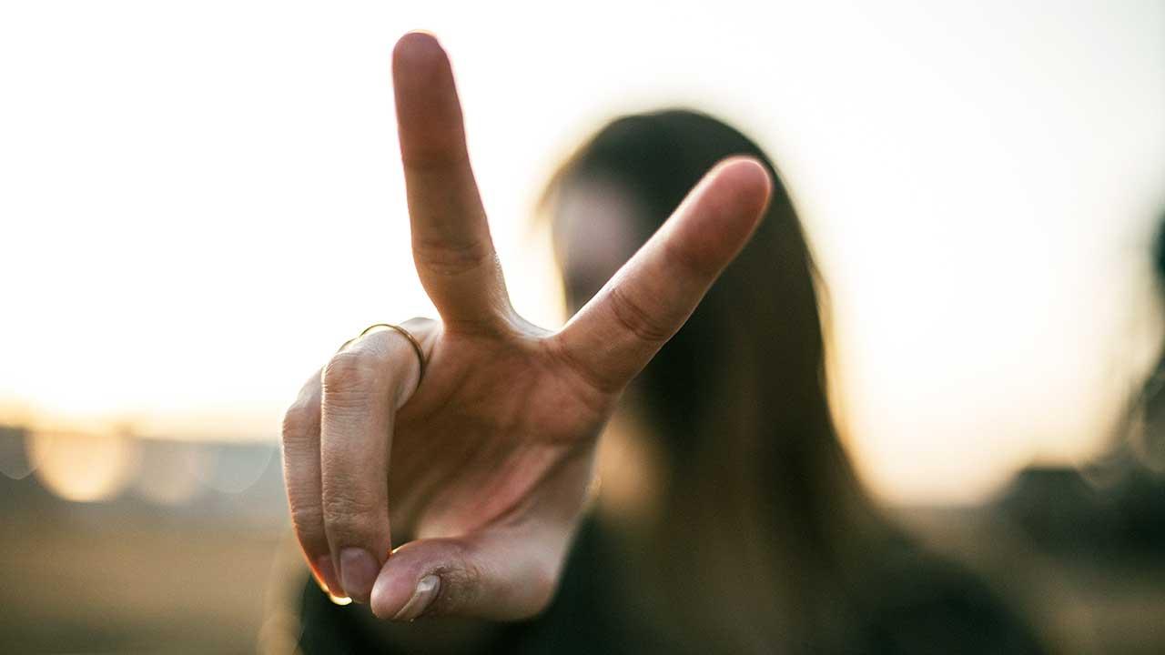 Junge Frau macht Victory-Zeichen