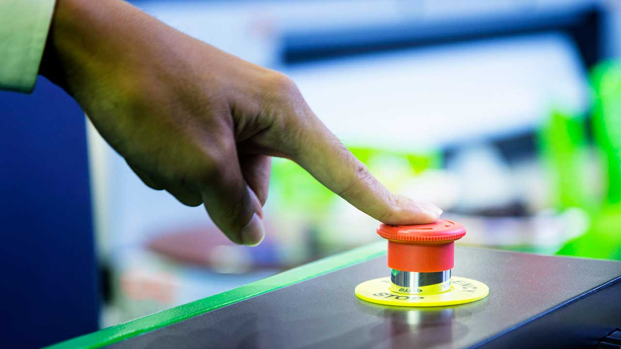 Hand drückt mit Zeigefinger auf roten Knopf zum Abschalten