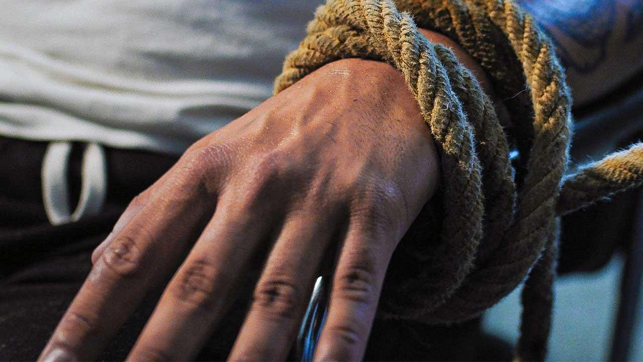 Hand ist mit einem Seil gebunden