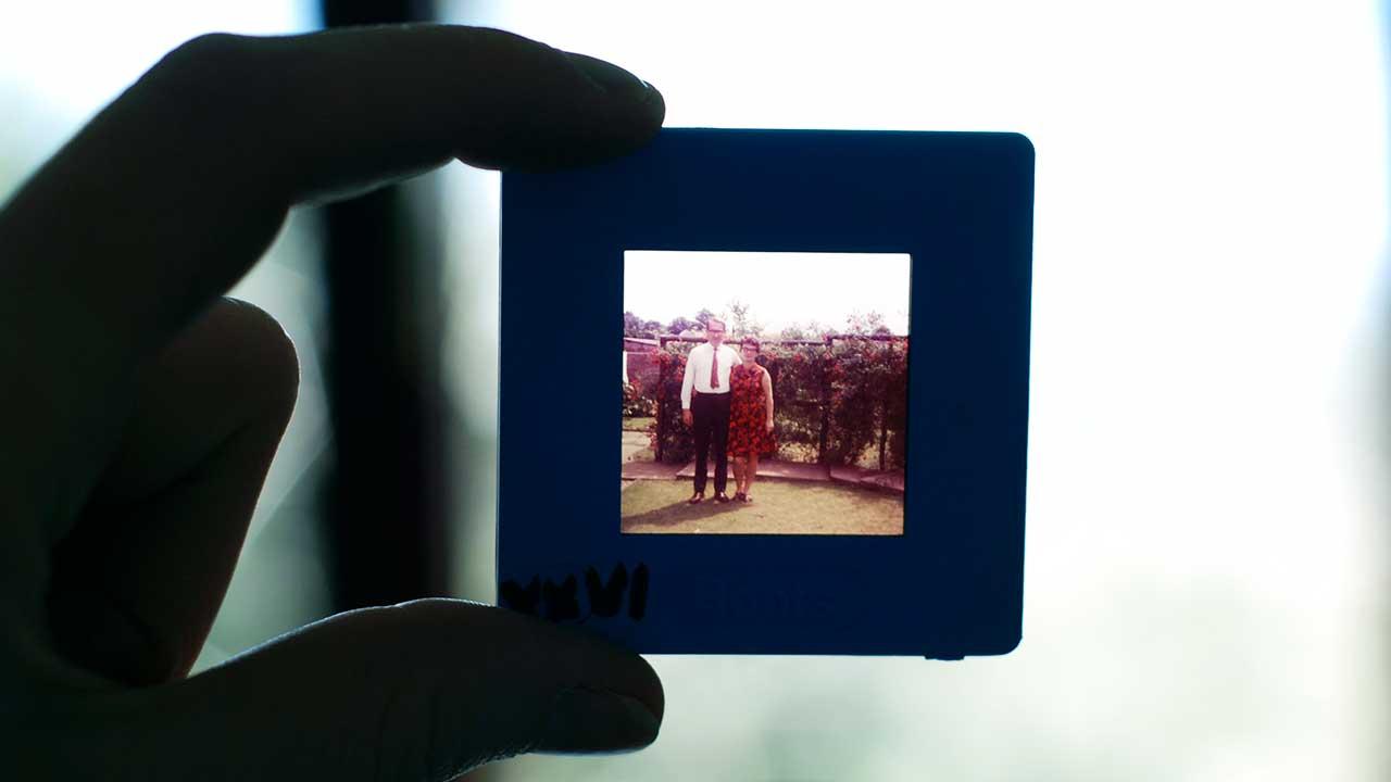 Hand hält Dia mit Foto der Eltern