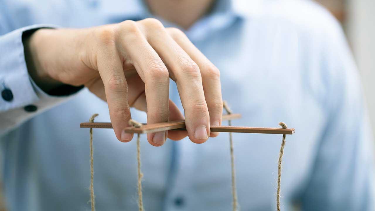 Hand hält Marionettenkreuz mit Fäden