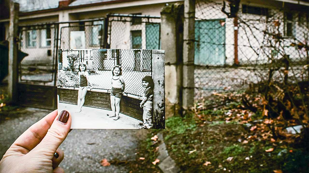 Frau hält Foto in der Hand, das die Frau als Mädchen mit zwei Kinderfreundinnen zeigt