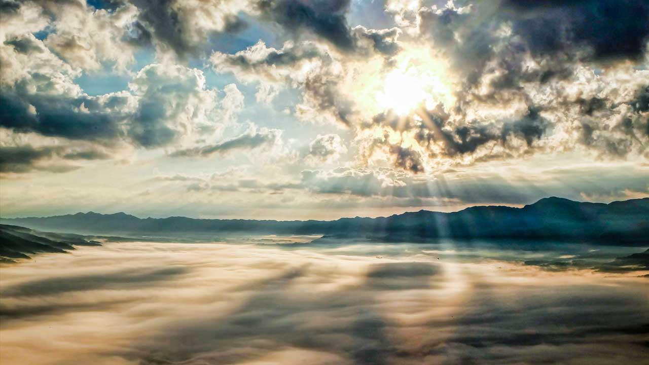Landschaft mit Nebel, Wolken und Sonnenlicht