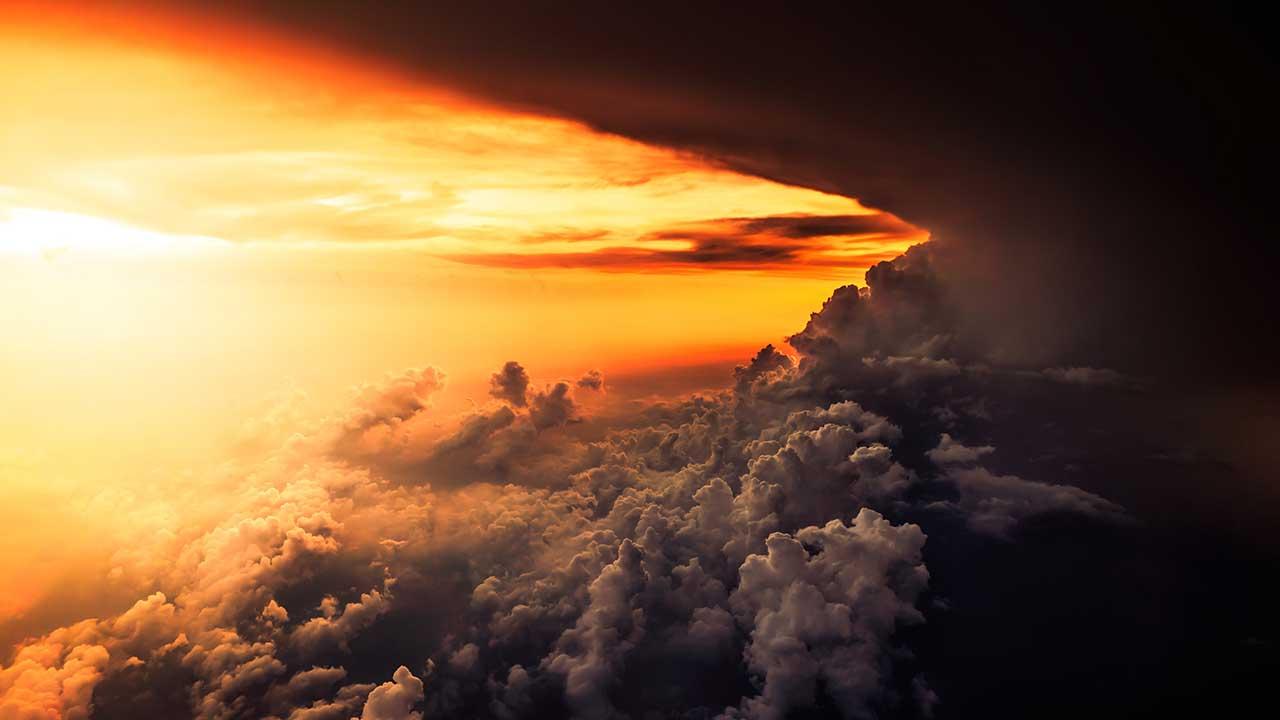 gelb-orange leuchtender Himmel neben dunklen Wolken