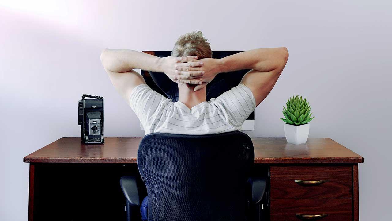 Rückansicht auf einen Mann, der zuhause arbeitet und gerade seine Arme hinter dem Kopf verschränkt