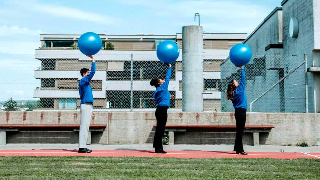Drei Models der Kleidermarke Homerun halten einen blauen Gymnastikball hoch