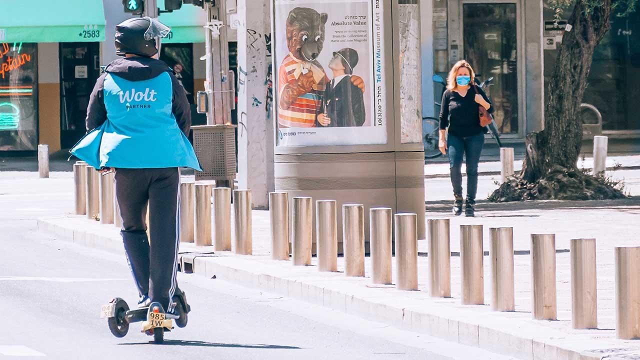 Fussgängerin und Rollerfahrer auf dem Rabin Square in Tel Aviv