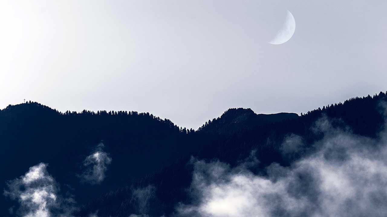 Nebelschwaden und zunehmender Mond über Mühlwald, Südtirol, Italien