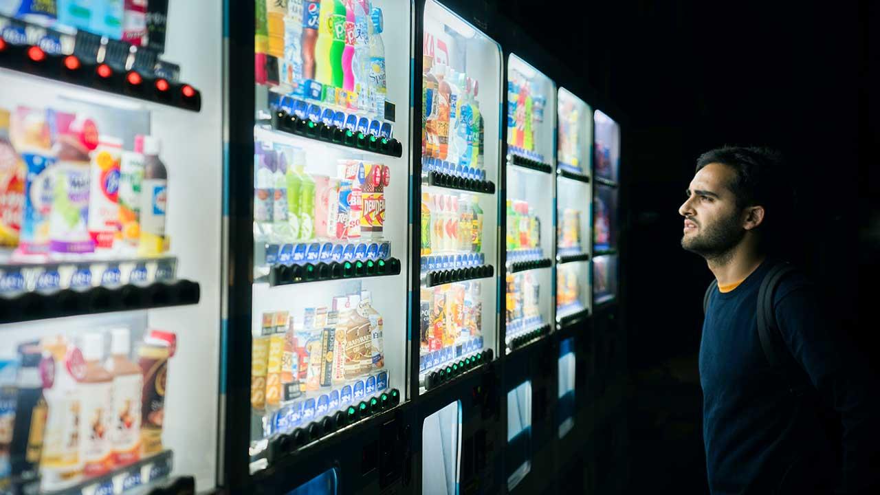Nicht-Japaner blickt in Tokio an Automaten mit Getränkeflaschen