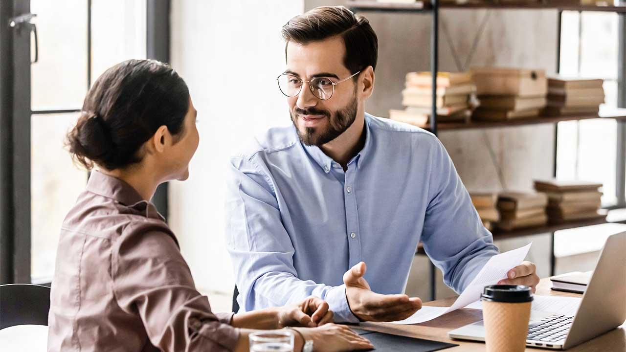 Chef im Gespräch mit einer Auszubildenden