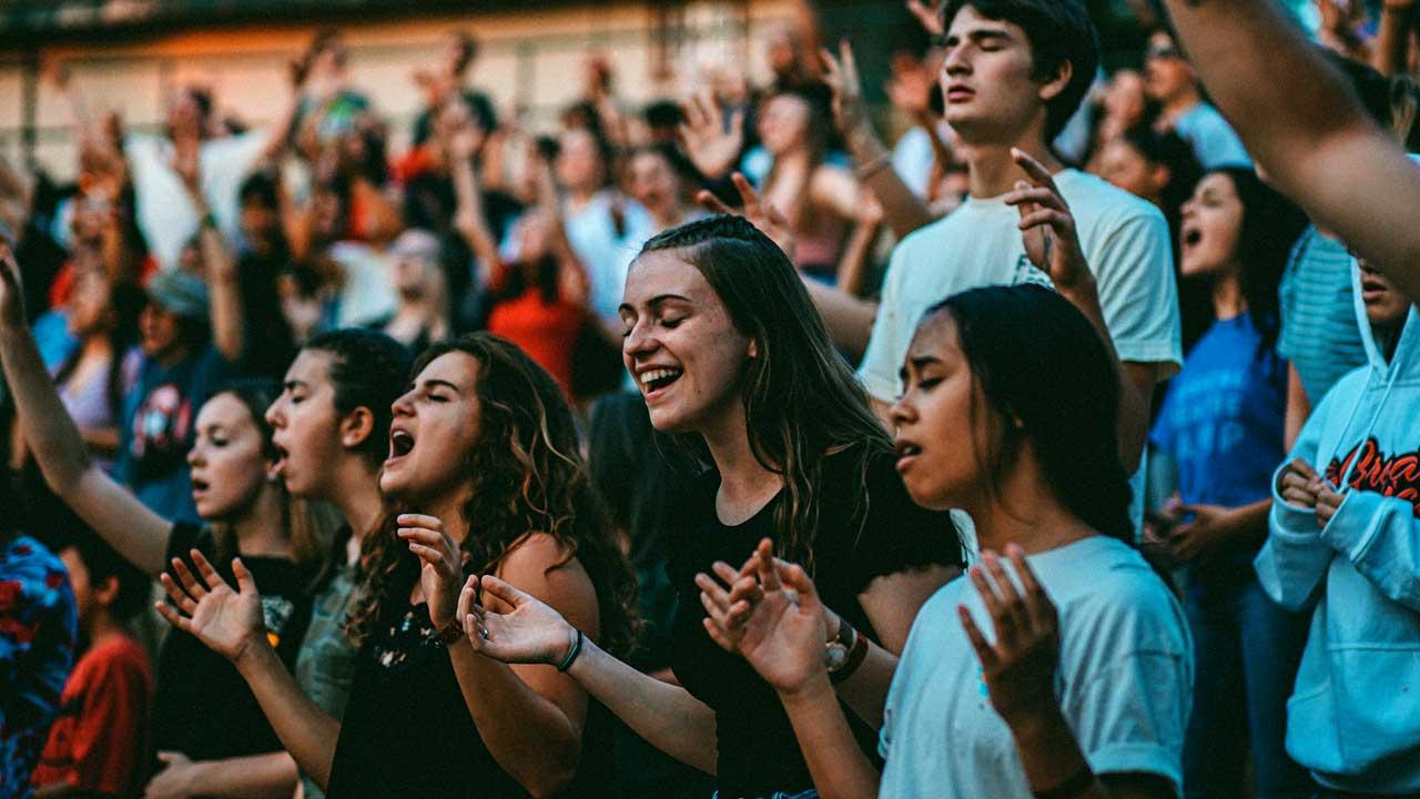Jugendliche und junge Erwachsene im Freien während eines Gottesdienstes