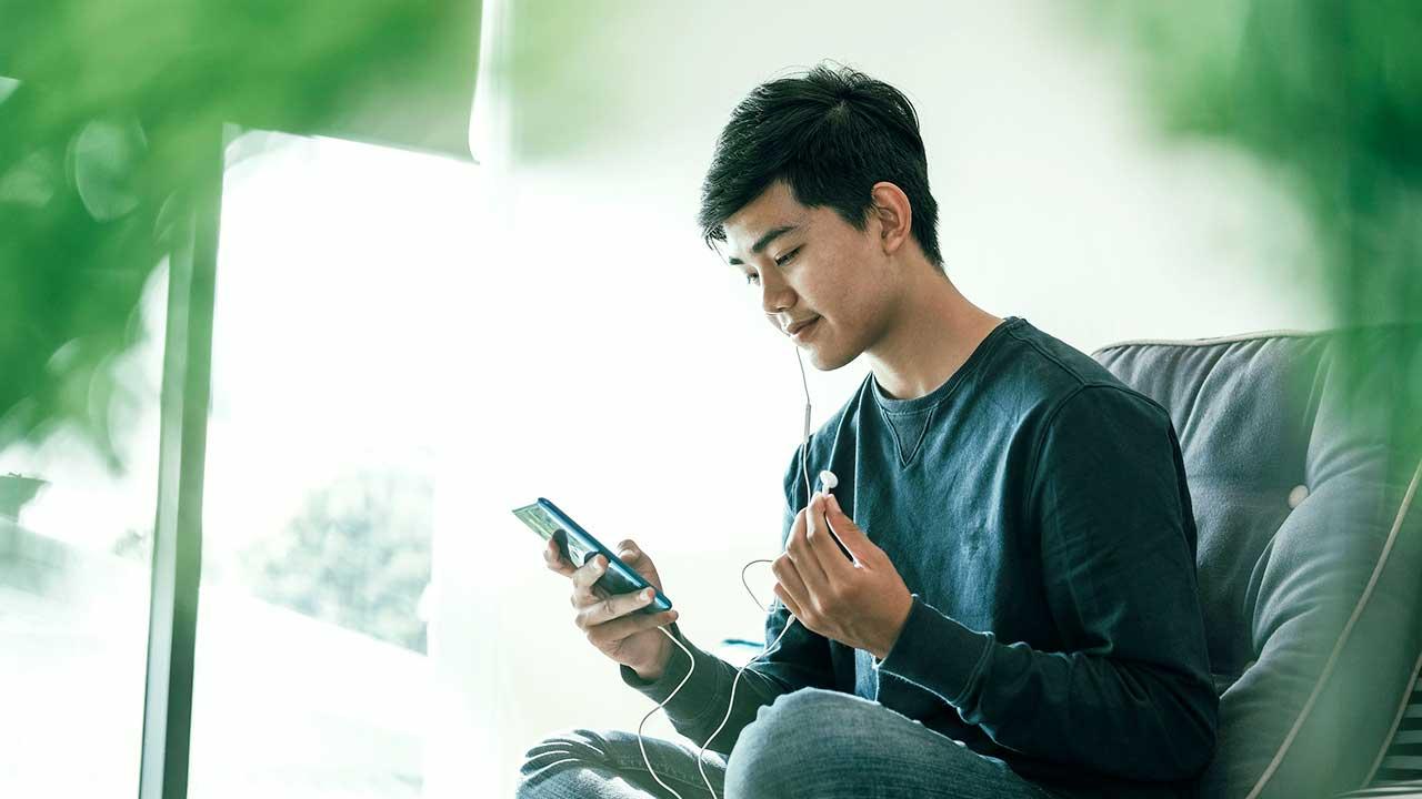 Jugendlicher mit Smartphone und Kopfhörern