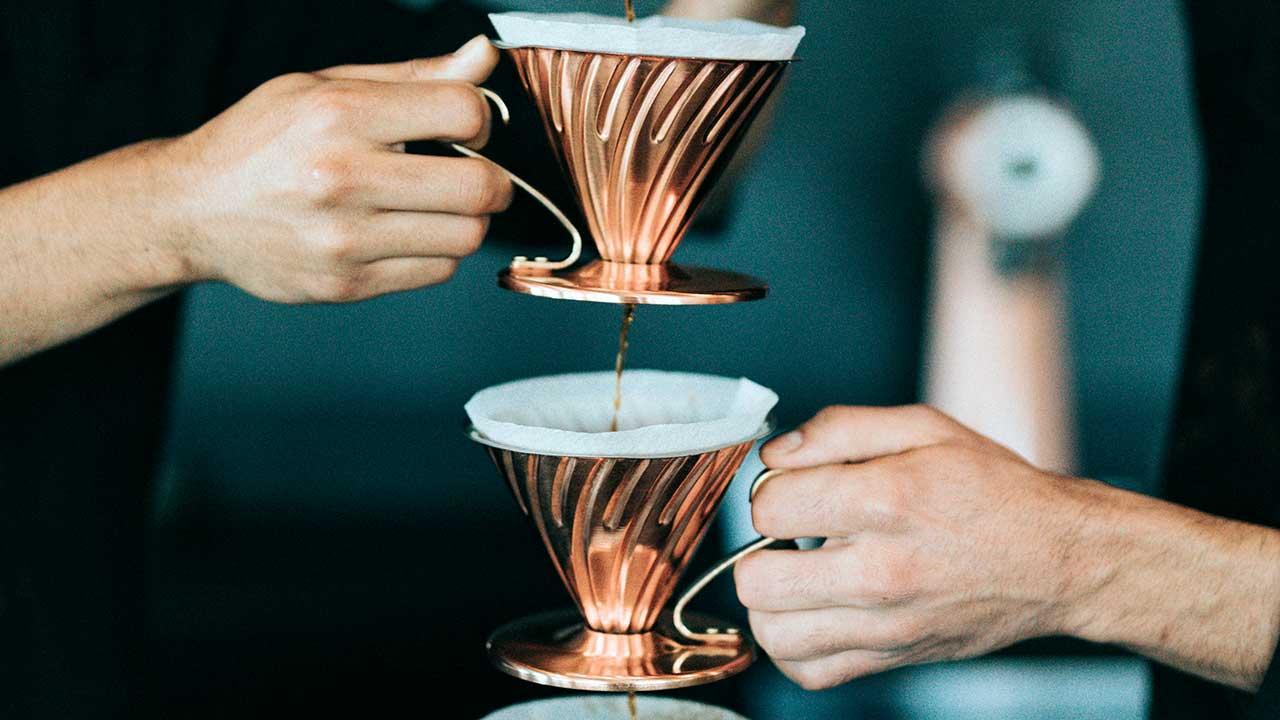 Hände halten Gefässe mit Kaffeefiltern, durch die Kaffee fliesst
