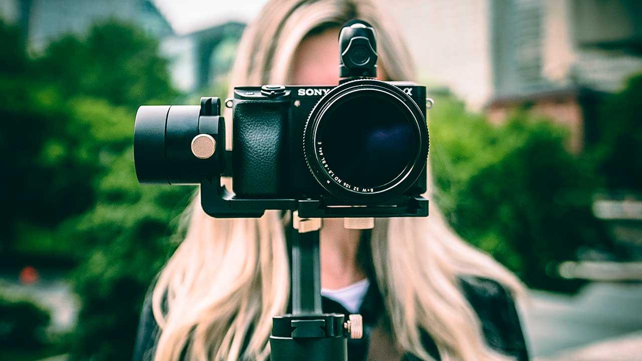Frau mit Gesicht hinter einer Kamera