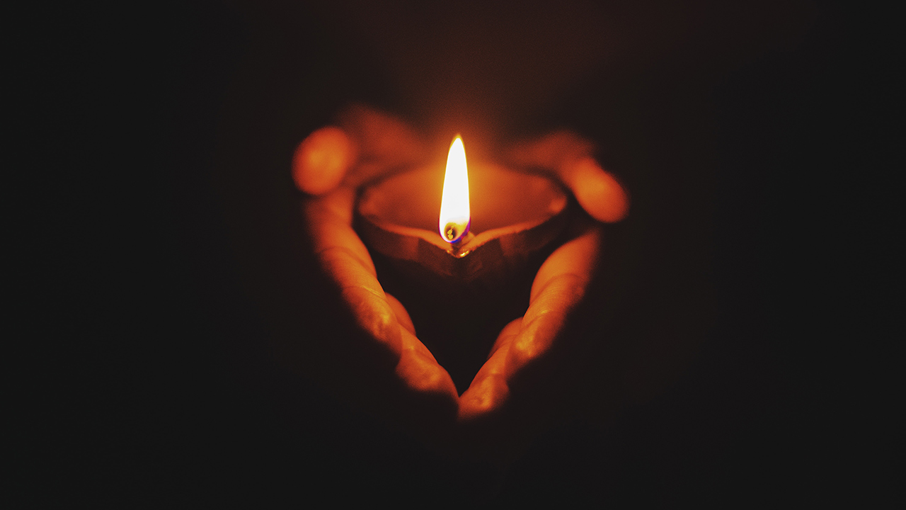 Eine Person hält eine brennende Kerze in den Händen.
