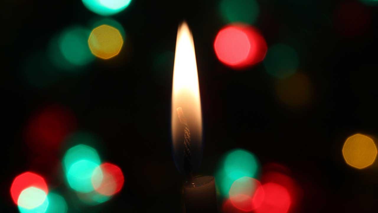 Kerzenflamme, im Hintergrund grüne und rote Lichtpunkte