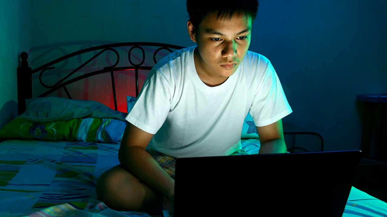 Teenager ist nachts am Laptop zugange
