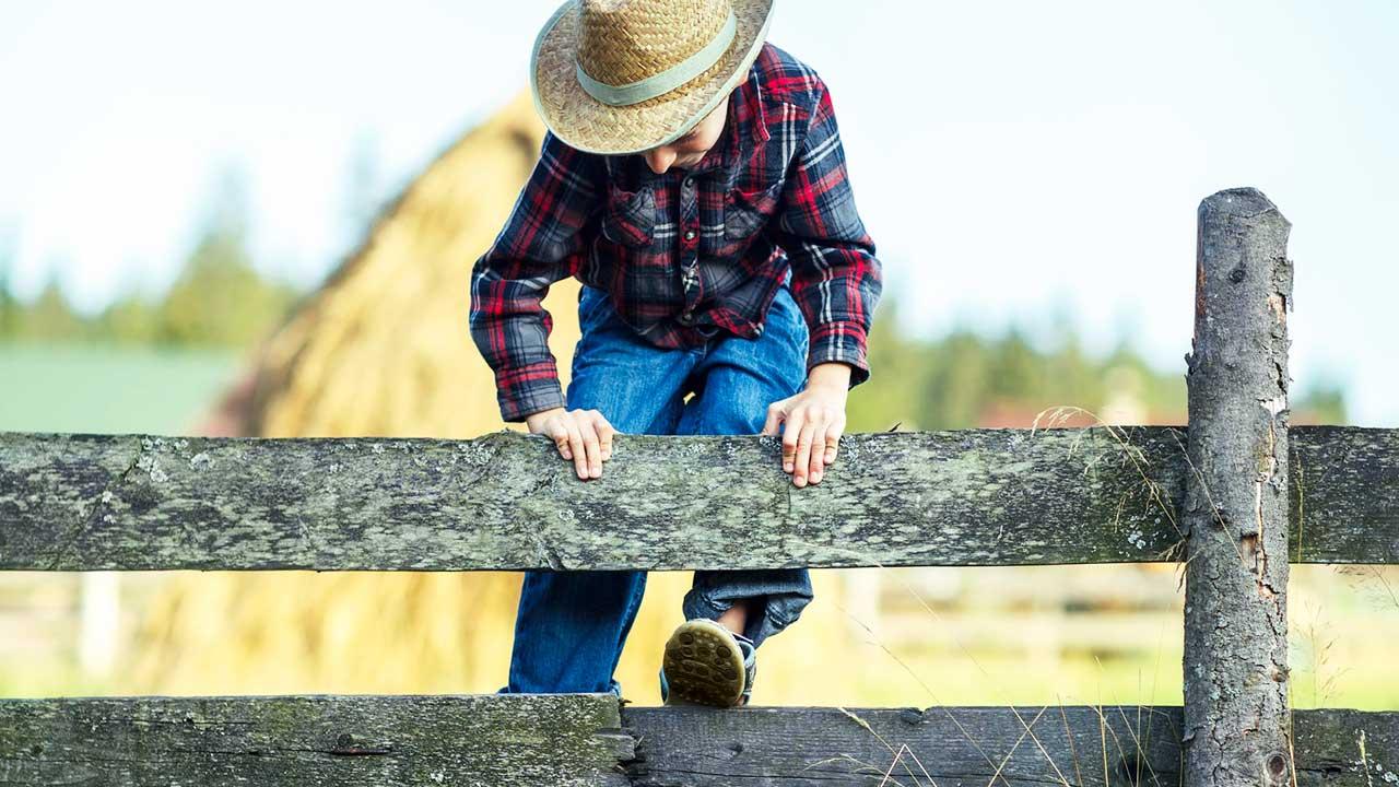 Junger Cowboy übersteigt Zaun