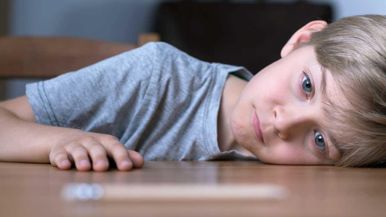 Gelangweilter Junge mit seinem Kopf auf dem Tisch