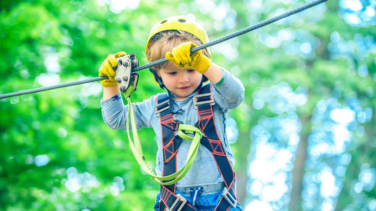 Junge klettert an einem Seil, mit einem Sicherheitsgurt abgesichert
