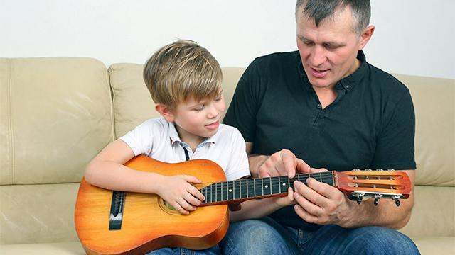 Vater zeigt gegenüber seinem Sohn Lernen des Gitarrenspiels Geduld