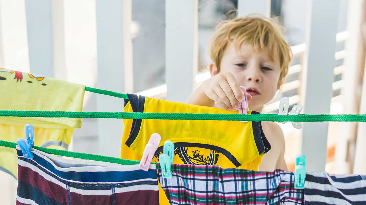Junge hängt Wäsche auf