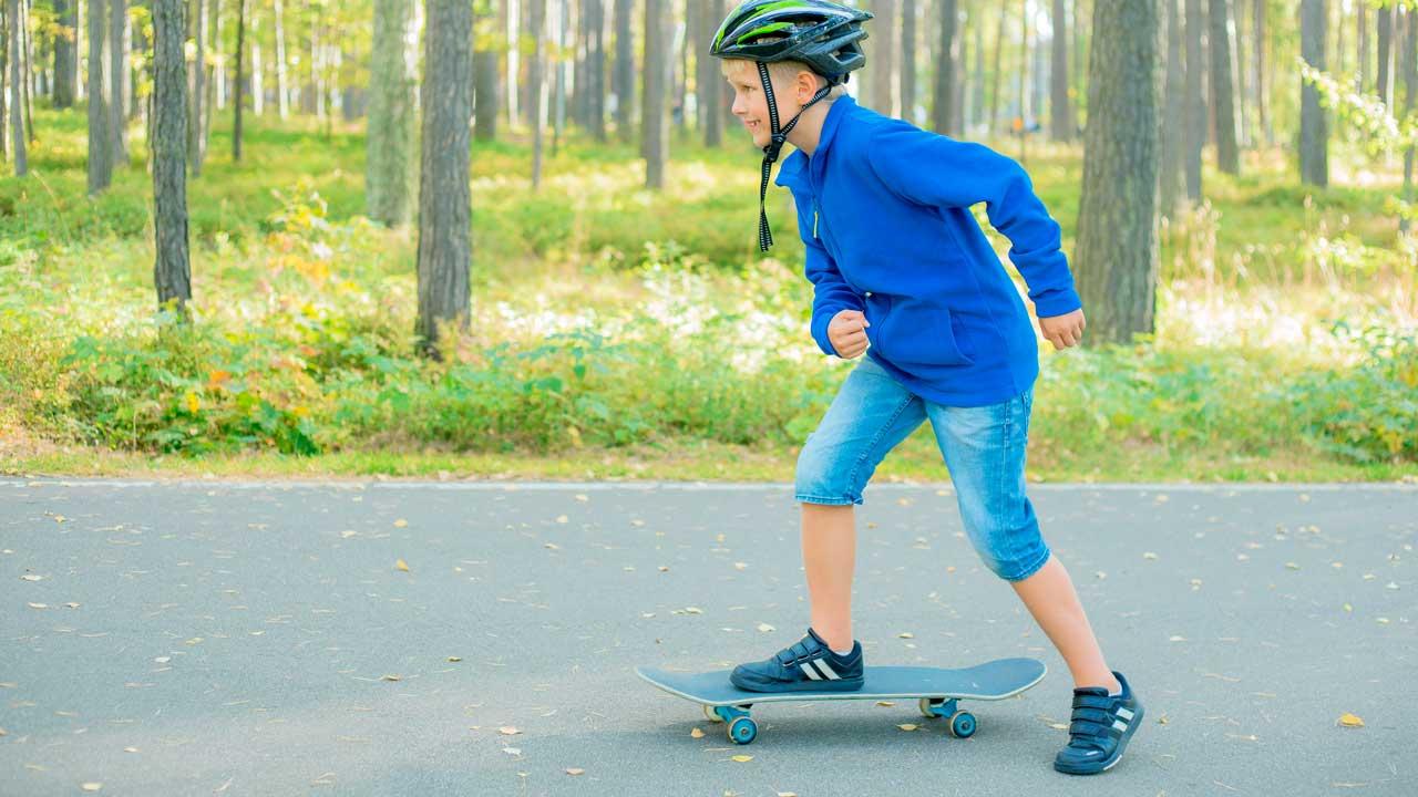 Jung setzt einen Fuss auf ein Skateboard und ist daran, loszufahren