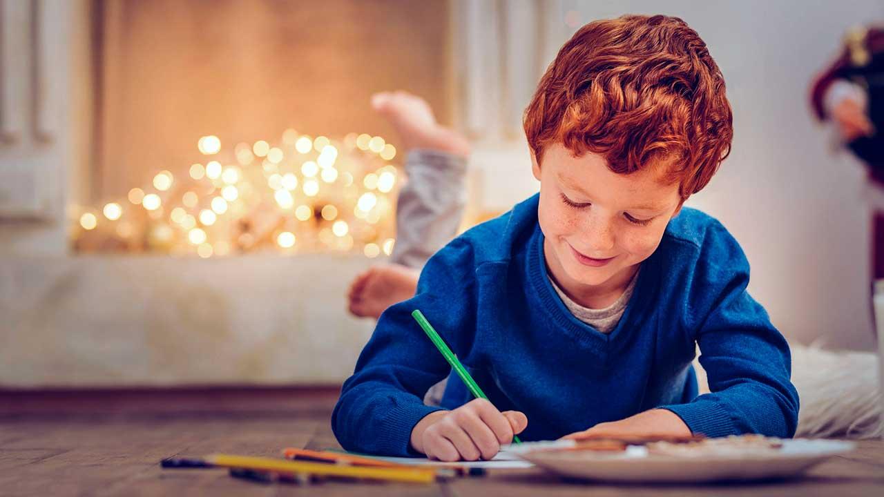 Junge liegt am Boden und schreibt einen Brief, im Hintergrund sind Lämpchen