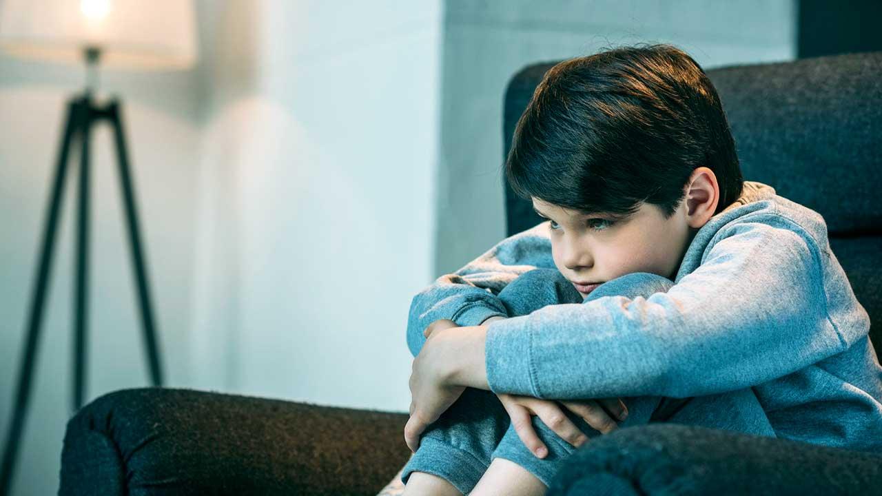 Frustrierter Junge sitzt auf einem Sofa