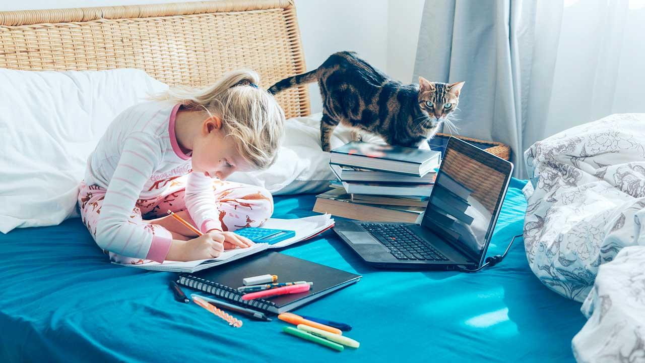 Mädchen lernt auf ihrem Bett, mit Büchern und Laptop