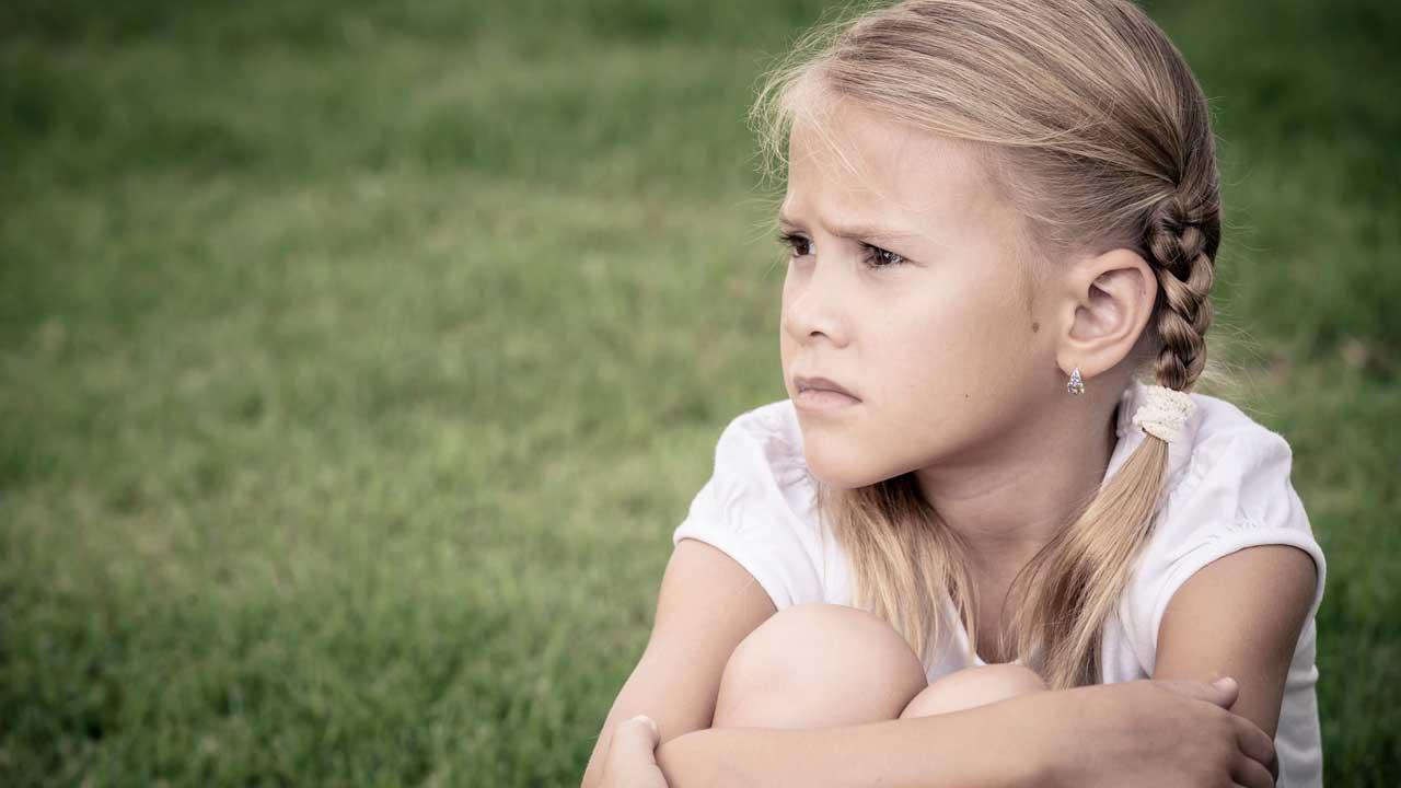 Mädchen schaut sorgenvoll von sich weg