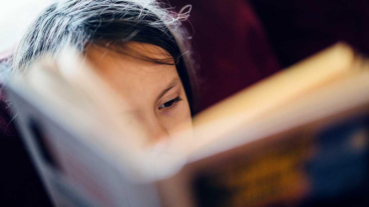 Mädchen liest voller Konzentration ein Buch