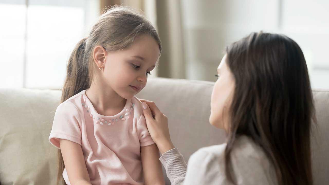 Frau tröstet ihre Tochter, welche auf dem Sofa sitzt