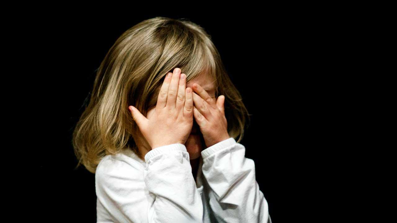 Mädchen hält Hände vor das Gesicht, aus Angst und Furcht