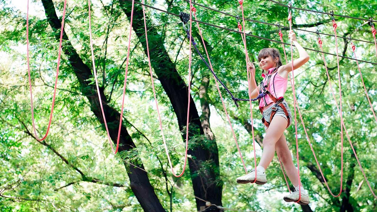 Mädchen bewegt sich im Kletterpark vorwärts