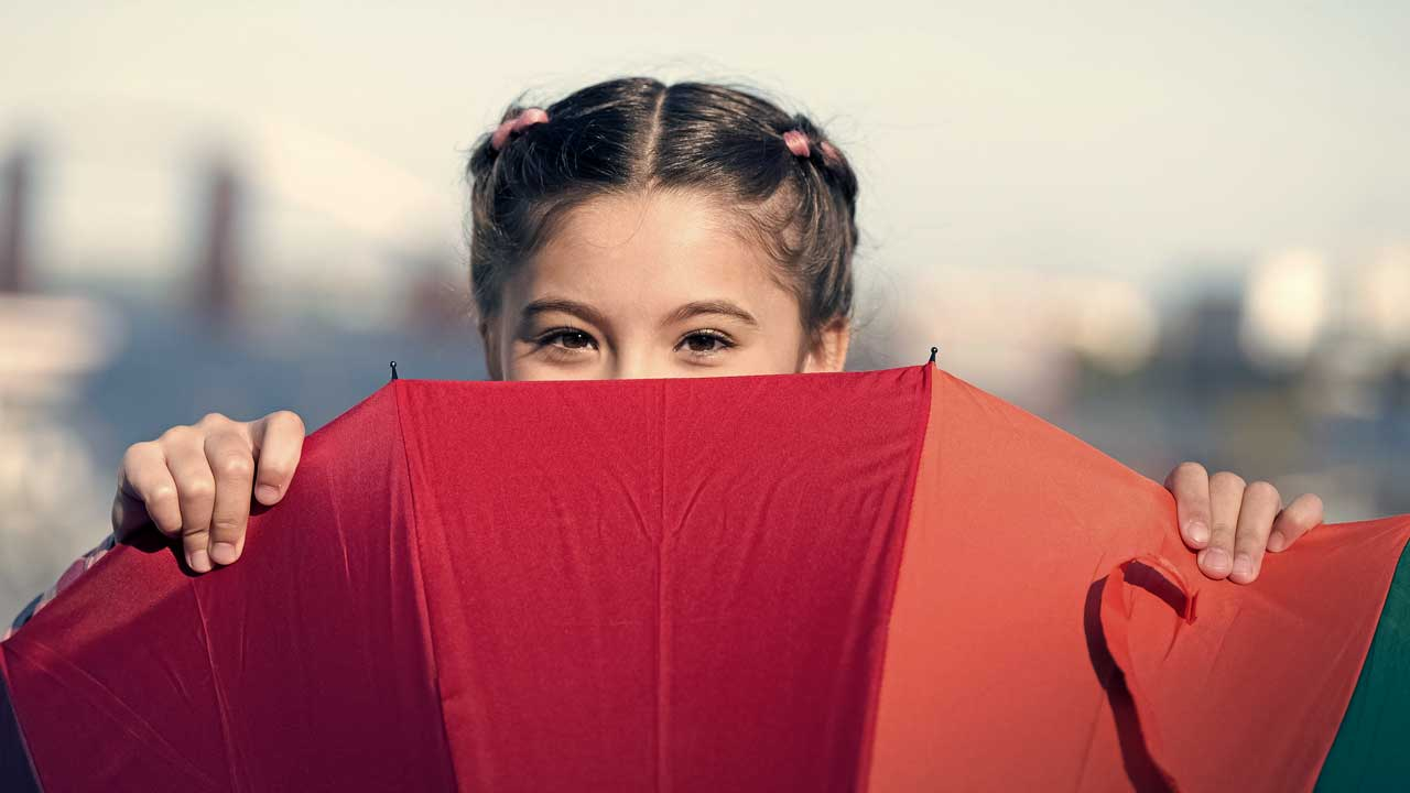 Mädchen versteckt sich hiner einem Regenschirm, den sie vor sich hält
