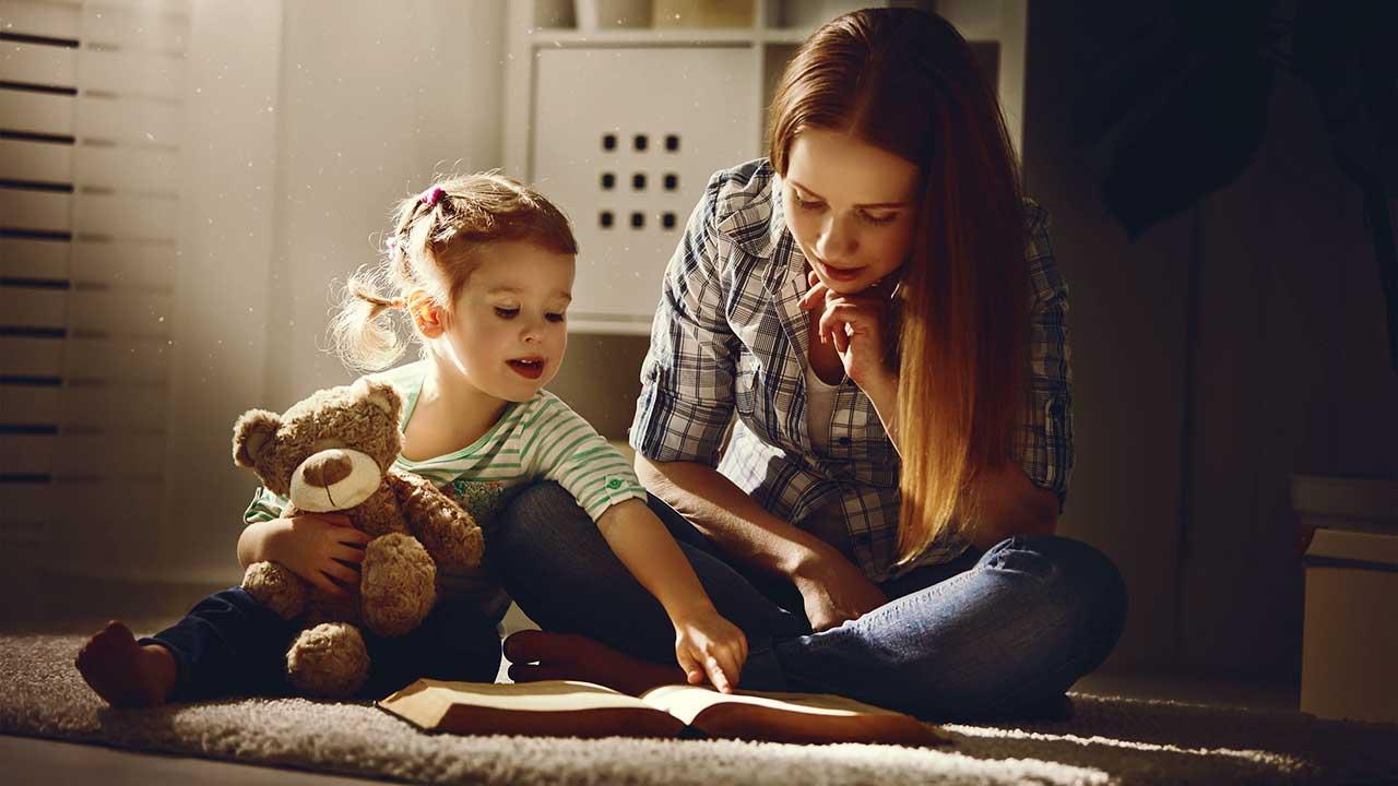 Mädchen und Mutter blicken zusammen in ein Buch