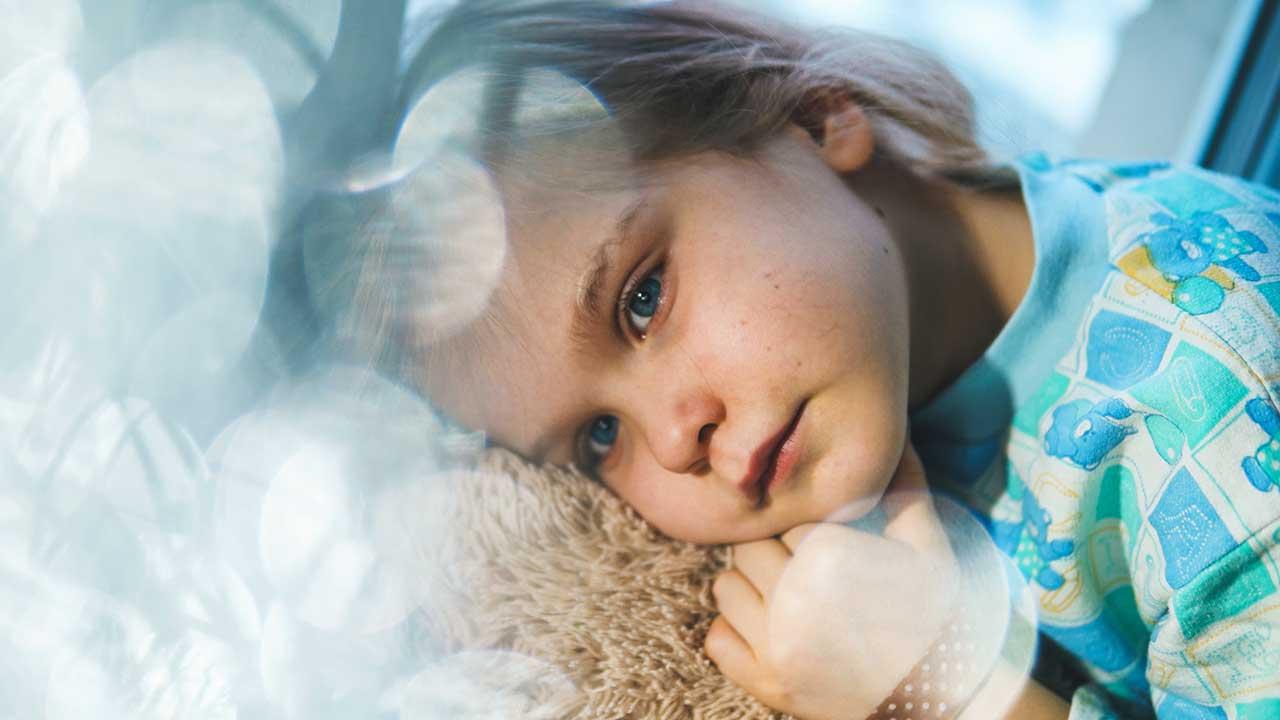 krankes Mädchen liegt auf einem Teddybär