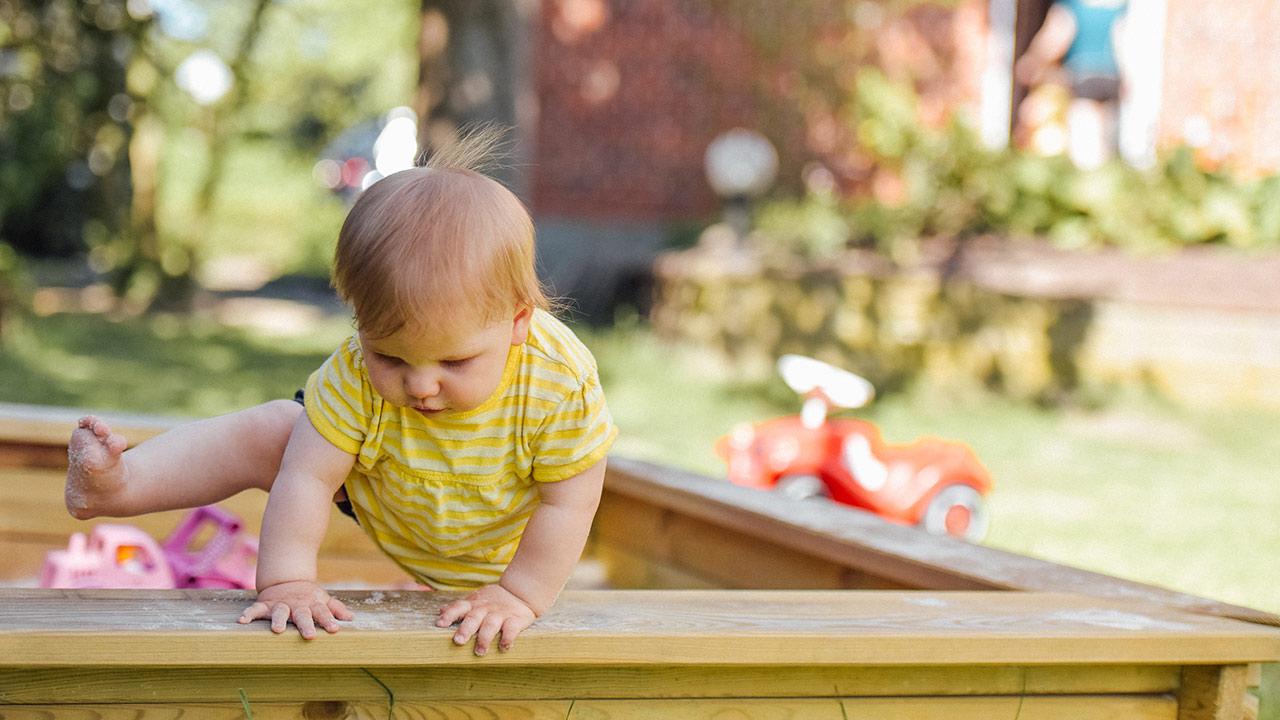 Ein Kind steigt aus dem Sandkasten.