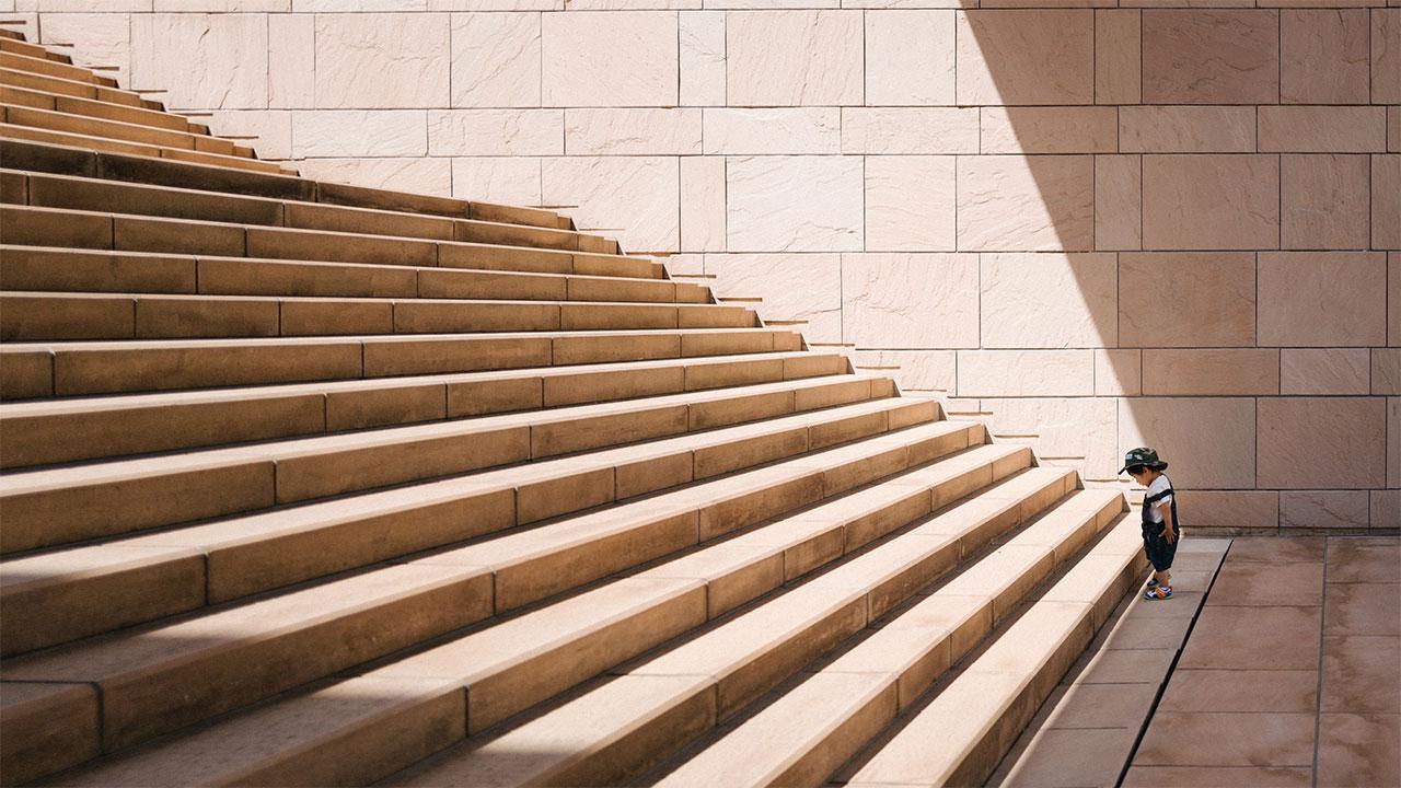 Ein Kleinkind steht vor einer grossen Treppe.