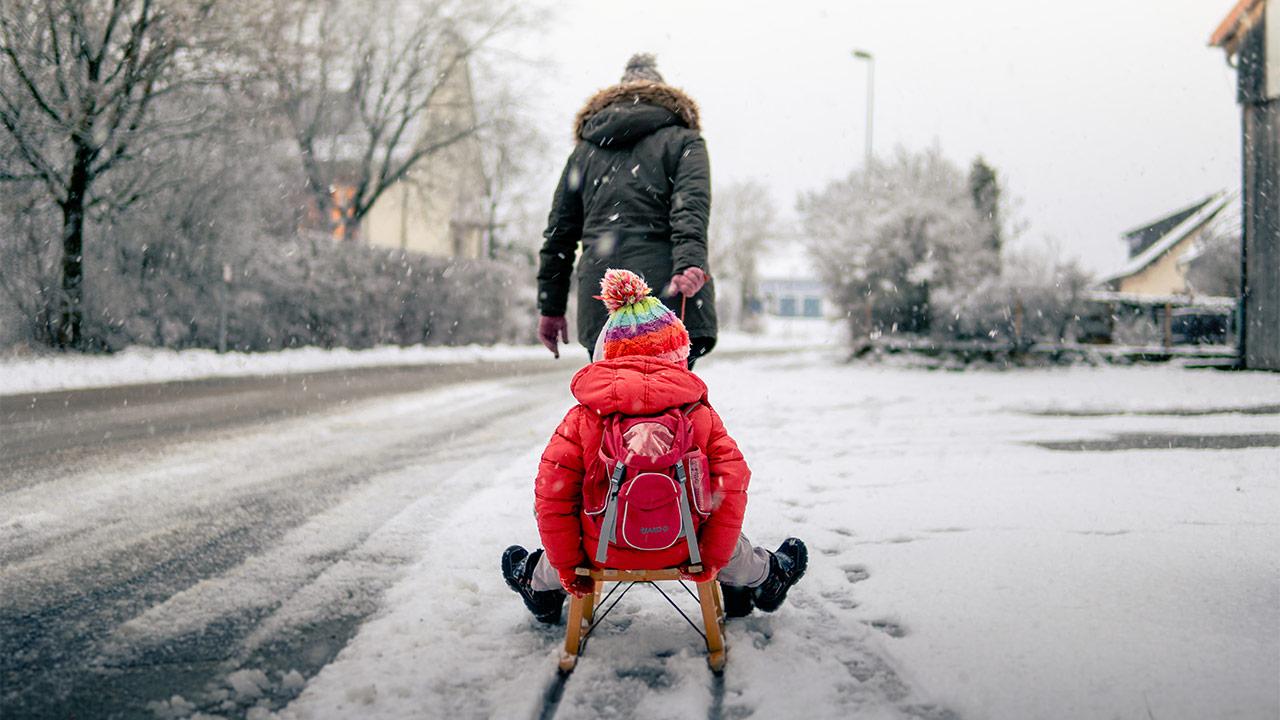 Erwachsene Person zieht Kind auf dem Schlitten.