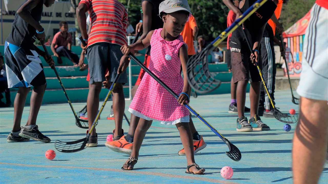Kinder spielen auf einem Sportplatz Hockey