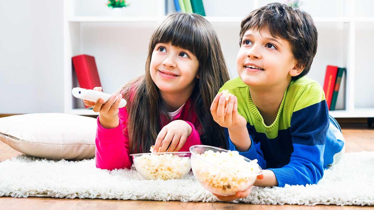 Mädchen und Junge schauen Fernsehen