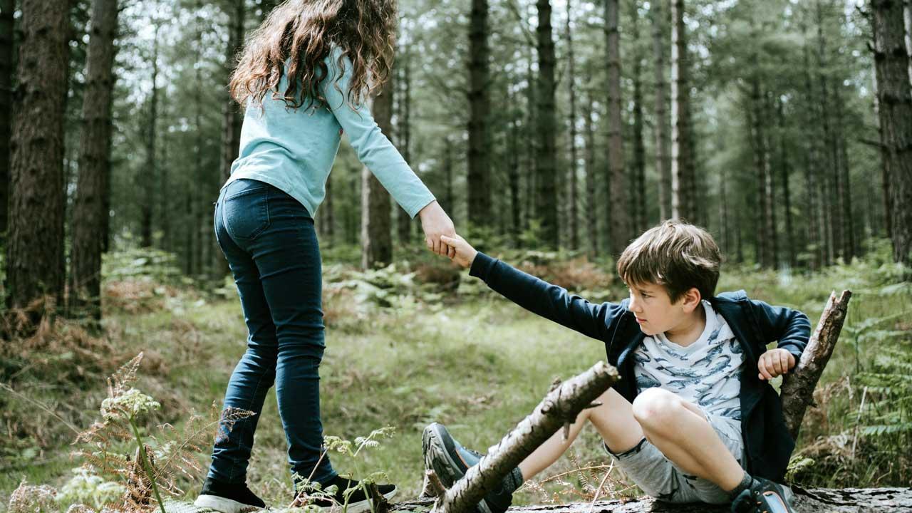 Mädchen hilft einem Jungen wieder auf die Beine