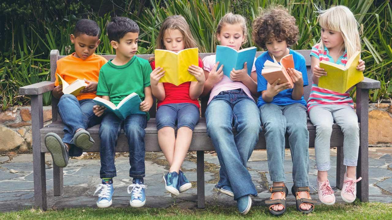 Eine Gruppe von Kindern sitzt auf einer Bank und liest