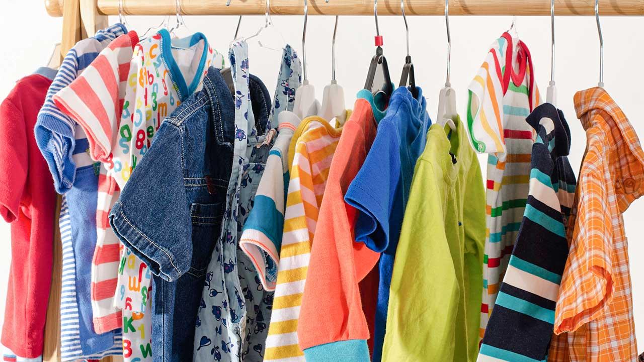 verschiedene Kinderkleider an einer Holzstange aufgehängt