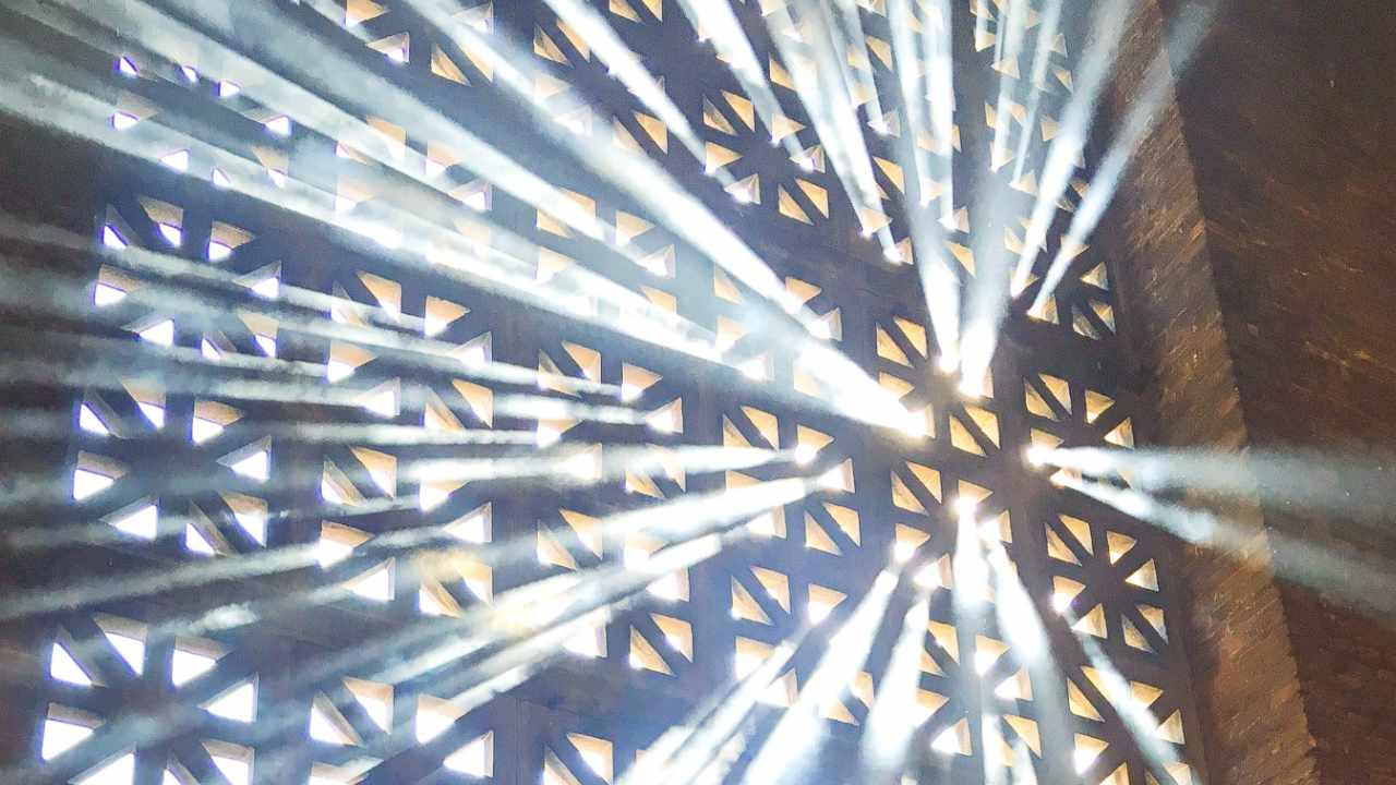 Sonnenstrahlen dringen durch das Gitterfenster eines Kirchengebäudes