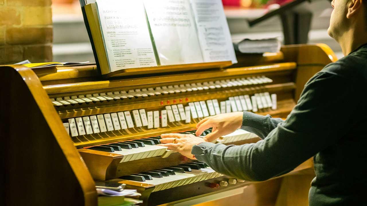 Organist spielt Kirchenorgel