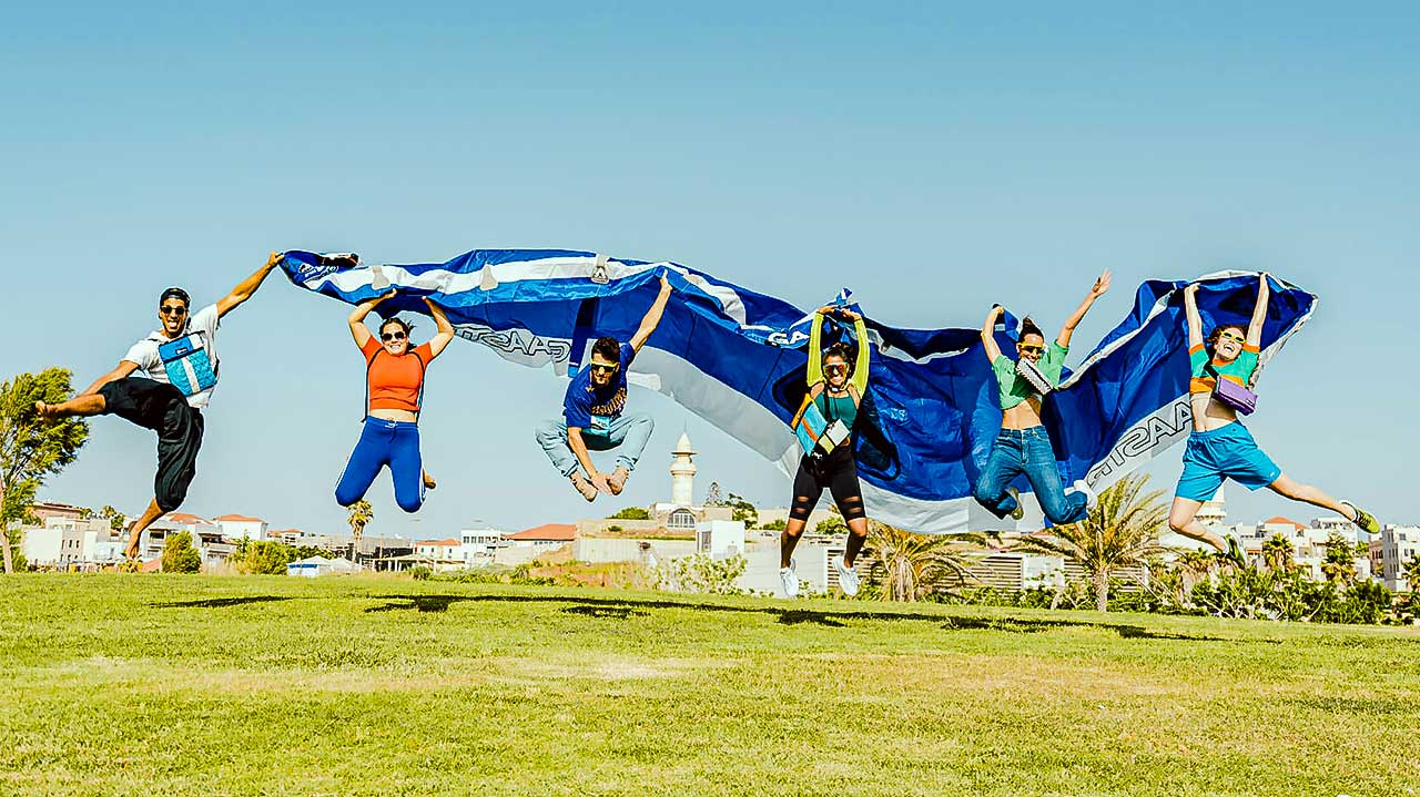 Junge Menschen springen mit einem Kitesurfing-Fallschirm hoch